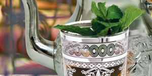 tea pot and cups of tea with mint leaves